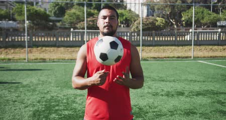 fotbal : Portrait of a mixed race male football player wearing sportswear, looking at camera, holding a football, standing on a sports field, in slow motion