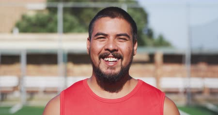 fotbal : Portrait of a happy mixed race male football player wearing sportswear, looking at camera, smiling, standing on a sports field, in slow motion