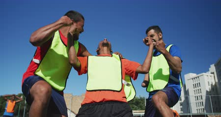 fotbal : Front view of a multi-ethnic group of male football players wearing sportswear and coloured bibs, training at a sports field in the sun, celebrating victory, in slow motion