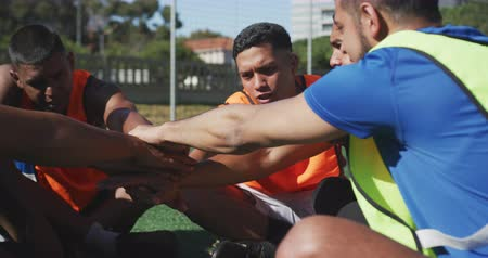 fotbal : Front view of a multi-ethnic group of male football players wearing sportswear and coloured bibs, training at a sports field in the sun, hand stacking, in slow motion
