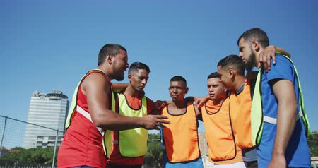 fotbal : Low angle front view of a multi-ethnic group of male football players wearing sportswear and coloured bibs, training at a sports field in the sun, standing in huddle, talking, motivating, in slow motion