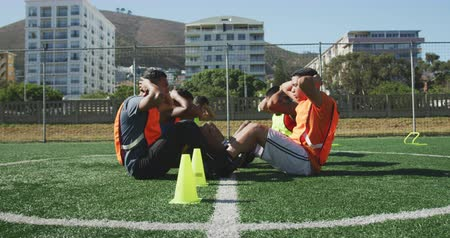 fotbal : Side view of a multi-ethnic group of football players players wearing sportswear and coloured bibs, training at a sports field in the sun, doing sit ups in a row, in slow motion