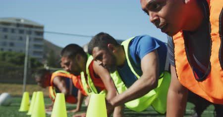 конусы : Front view of a multi-ethnic group of male football players wearing sportswear and coloured bibs, training at a sports field in the sun, doing press ups in a row and touching cones, in slow motion