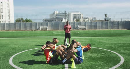 пять : Side view of a multi-ethnic group of male soccer players wearing sportswear and coloured bibs, training at a sports field in the sun, doing sit ups in a row, their coach standing in the background, in slow motion