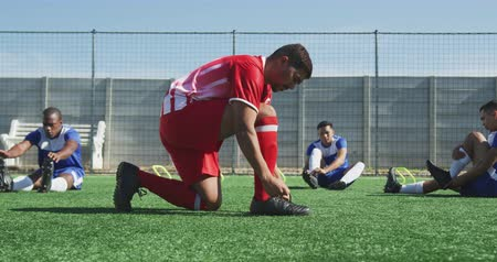 fotbal : Side view of a mixed race male football player on the pitch during a five a side football match on a sunny day, tying shoelaces, with his teammates in the background, in slow motion Dostupné videozáznamy