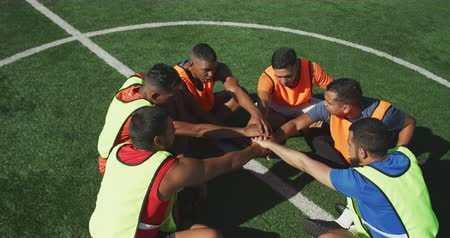 fotbal : High angle view of a multi-ethnic group of male football players wearing sportswear and coloured bibs, training at a sports field in the sun, hand stacking, in slow motion