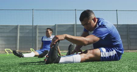 fotbal : Side view of two mixed race male football players wearing a team strip, training at a sports field in the sun, warming up, stretching, in slow motion