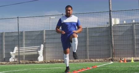 fotbal : Front view of a mixed race male football player wearing a team strip, training at a sports field in the sun, running and skipping, in slow motion Dostupné videozáznamy