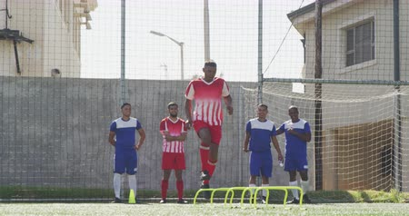 leaping : Front view of a multi-ethnic group of male football players wearing a team strip, training at a sports field in the sun,jumping over low hurdles in slow motion