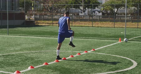 fotbal : Rear view of a mixed race male football player wearing a team strip, training at a sports field in the sun, running and skipping, in slow motion