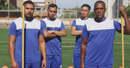 fotbal : Front view of a multi-ethnic group of male football players wearing a team strip, training at a sports field in the sun, standing and looking at camera in slow motion Dostupné videozáznamy