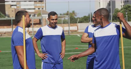 jogador de futebol : Front view of a multi-ethnic group of male football players wearing a team strip, training at a sports field in the sun, talking and interacting in slow motion Stock Footage