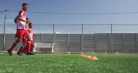 fotbal : Side view of a multi-ethnic group of male football players wearing a team strip, training at a sports field in the sun, running and touching cones, in slow motion Dostupné videozáznamy