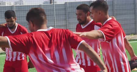 fotbal : Front view of a multi-ethnic group of male football players wearing a team strip, training at a sports field in the sun, stretching legs with hands on each other shoulders, in slow motion Dostupné videozáznamy