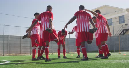 jogador de futebol : Rear view of a multi-ethnic group of male football players wearing a team strip, training at a sports field in the sun, stretching legs balancing on one leg, in slow motion