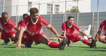 fotbal : Front view of a multi-ethnic group of male football players wearing a team strip, training at a sports field in the sun, stretching, in slow motion Dostupné videozáznamy