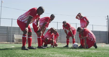 fotbal : Side view of a multi-ethnic group of male football players wearing a team strip, training at a sports field in the sun, resting with a ball next to them, in slow motion