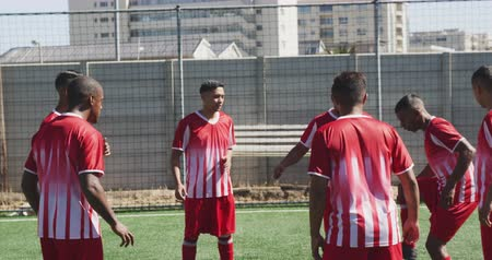 패스 : Front view of a multi-ethnic group of male football players wearing a team strip, training at a sports field in the sun, kicking and passing a ball, in slow motion