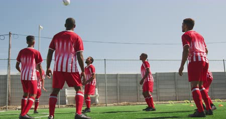 chutando : Front view of a multi-ethnic group of male football players wearing a team strip, training at a sports field in the sun, kicking and passing a ball, in slow motion