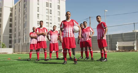 fotbal : Front view of a multi-ethnic group of male football players wearing a team strip, training at a sports field in the sun, standing next to each other, one player with prosthetic leg holding a ball, looking at camera, in slow motion