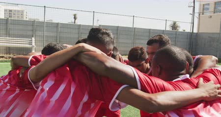 fotbal : Front view of a multi-ethnic group of male football players wearing a team strip, training at a sports field in the sun, embracing, standing in a huddle, motiviating, in slow motion