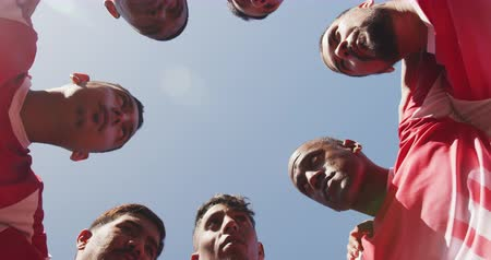 fotbal : Low angle view of a multi-ethnic group of male football players wearing a team strip, training at a sports field in the sun, embracing, standing in a huddle, motiviating, in slow motion