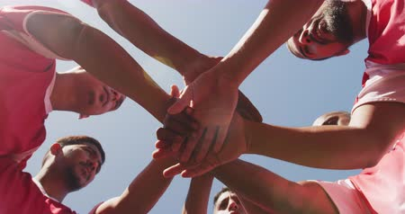 fotbal : Low angle view of a multi-ethnic group of male football players wearing a team strip, training at a sports field in the sun, hand stacking, standing in a huddle, motiviating, in slow motion