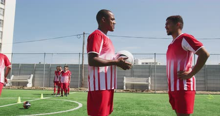 fotbal : Side view of two mixed race male football players wearing a team strip, training at a sports field in the sun, talking one of them holding a ball, with their teammates training in the background in slow motion