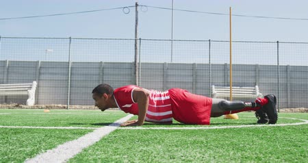 fotbal : Side view of a mixed race male football player with a prosthetic leg wearing a team strip, training at a sports field in the sun, doing push ups, in slow motion