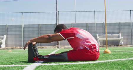 fotbal : Side view of a mixed race male football player with a prosthetic leg wearing a team strip, training at a sports field in the sun, stretching, in slow motion