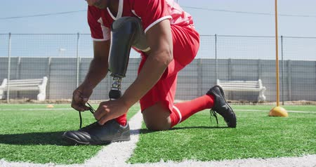 fotbal : Front view low section of a mixed race male football player with a prosthetic leg wearing a team strip, training at a sports field in the sun, tying his shoelaces, in slow motion Dostupné videozáznamy