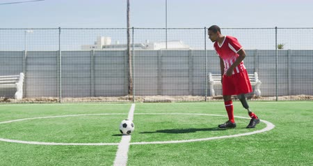 kop : Side view of a mixed race male football player with a prosthetic leg wearing a team strip, training at a sports field in the sun, kicking a ball, in slow motion Dostupné videozáznamy