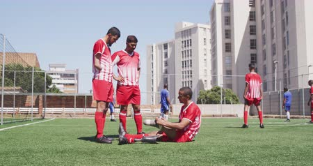 fotbal : Side view of a multi-ethnic group of male football players wearing a team strip, training at a sports field in the sun, a disabled player putting a prosthetic leg on and one player without a hand in slow motion Dostupné videozáznamy