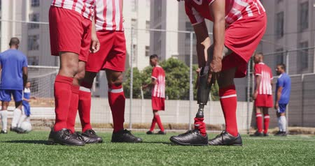 handicap : Side view mid section of a multi-ethnic group of male football players wearing a team strip, training at a sports field in the sun, a disabled player putting a prosthetic leg on, in slow motion