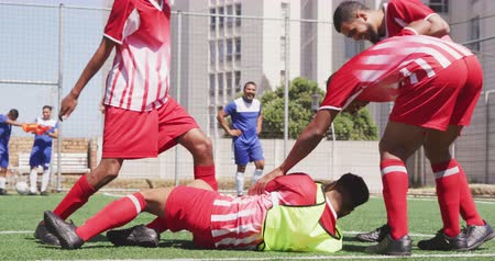 kop : Side view of a multi-ethnic group of male football players wearing a team strip, training at a sports field in the sun, celebrating scoring a goal, one of the players lying on the ground, in slow motion