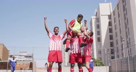 torcendo : Front view of a multi-ethnic group of male football players wearing a team strip, training at a sports field in the sun, holding one of their teammates on the shoulders, celebrating scoring a goal in slow motion Vídeos