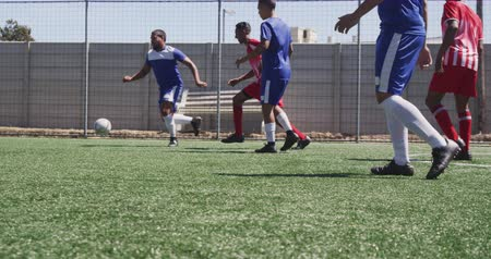 fotbal : Side view of a two multi-ethnic teams of male football players wearing a team strip, training at a sports field in the sun, playing a match, in slow motion