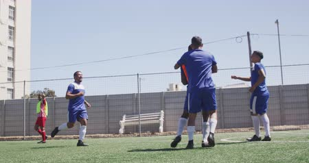 fotbal : Side view of a two multi-ethnic teams of male football players wearing a team strip, training at a sports field in the sun, playing a match, passing a ball, in slow motion Dostupné videozáznamy