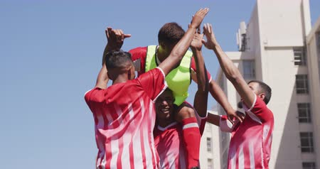 torcendo : Low angle front view of a multi-ethnic group of male football players wearing a team strip, training at a sports field in the sun, holding one of their teammates on the shoulders, celebrating scoring a goal in slow motion
