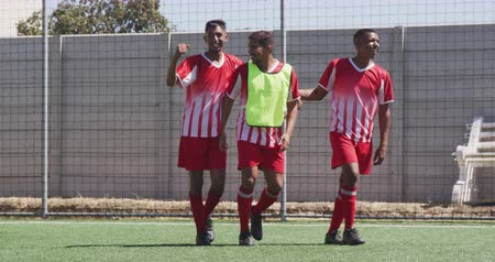torcendo : Front view of three mixed race male football players wearing a team strip, training at a sports field in the sun, playing a match, celebrating, in slow motion Vídeos
