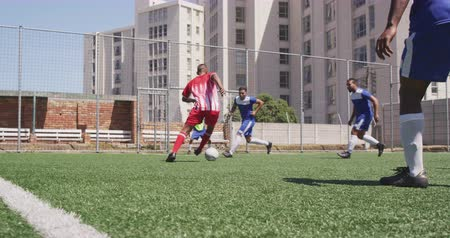 fotbal : Rear view of a two multi-ethnic teams of male football players wearing a team strip, training at a sports field in the sun, playing a match, scoring a goal, in slow motion