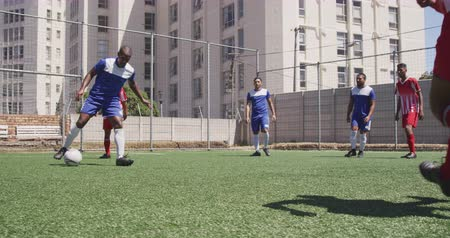 fotbal : Front view of a two multi-ethnic teams of male football players wearing a team strip, training at a sports field in the sun, playing a match, scoring a goal, in slow motion