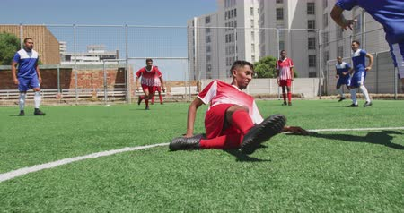 chutando : Rear view low section of a multi-ethnic group of male football players wearing a team strip, training at a sports field in the sun, playing a match, kicking a ball, tackling, in slow motion