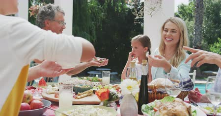 패스 : Side view close up of a multi-generation Caucasian family having a good time together, sitting in a garden, by a table with food on it, a kid is passing a bowl to a women, while a senior man is making