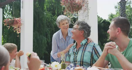 pocałunek : Side view close up of a multi-generation Caucasian family having a good time together, sitting in a garden, by a table with food on it, a senior couple are kissing each other on the cheeks, on a sunny day, in slow motion