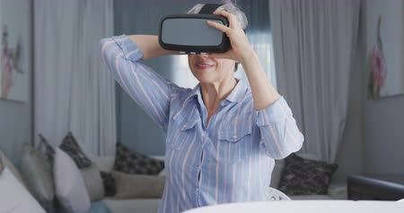 wizja : Front view of a senior Caucasian woman, having a good time in an apartment, putting on virtual reality headset, in slow motion