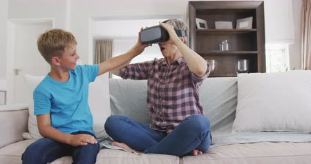 fejhallgató : Front view of a senior Caucasian woman, having a good time in an apartment, sitting on a couch with her grandson, using virtual reality headset, in slow motion Stock mozgókép