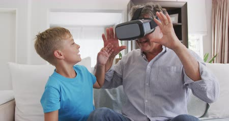 fejhallgató : Front view of a senior Caucasian man, having a good time in an apartment, sitting on a couch with his grandson, using virtual reality headset, playing, looking surprised, in slow motion