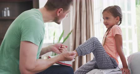 resting : Side view of a Caucasian man enjoying his time in an apartment, putting shoe on his daughter foot, tying it, in slow motion Stock Footage