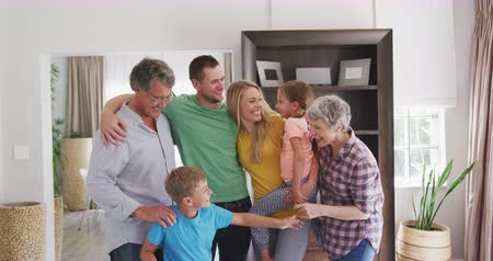 rodzeństwo : Front view of a multi-generation Caucasian family enjoying their time in an apartment, standing, embracing, smiling and talking, looking to the camera, in slow motion